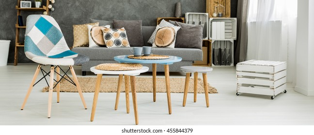 Panoramic picture of a coffee table set with a patchwork chair in a bright contemporary apartment