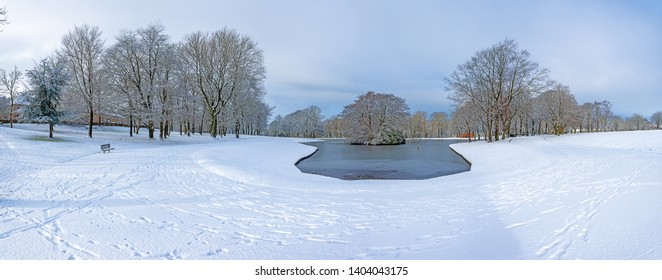 Panoramic picturesque snow scene with snow covered trees and frozen lake in the background Queens park Blackburn Lancashire