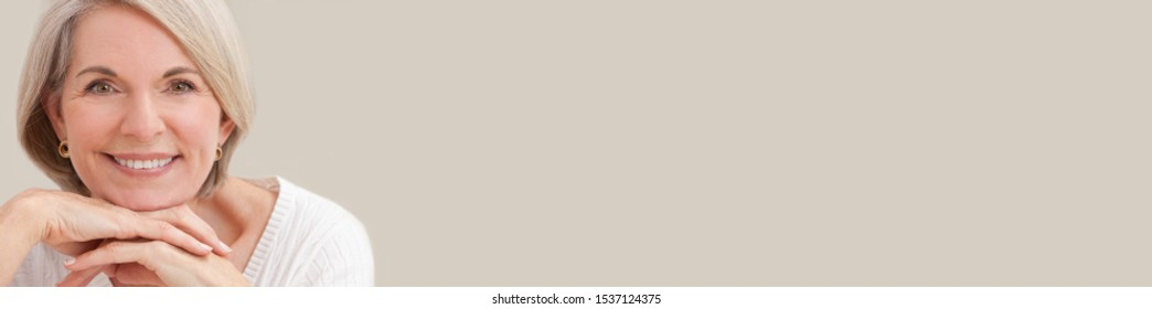 Panoramic portrait of an attractive elegant senior woman relaxing at home panorama web banner with copy space