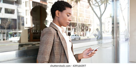 Panoramic portrait of beautiful african american business woman with reflective office building in financial city using smart phone, outdoors. Professional black woman technology lifestyle, exterior.