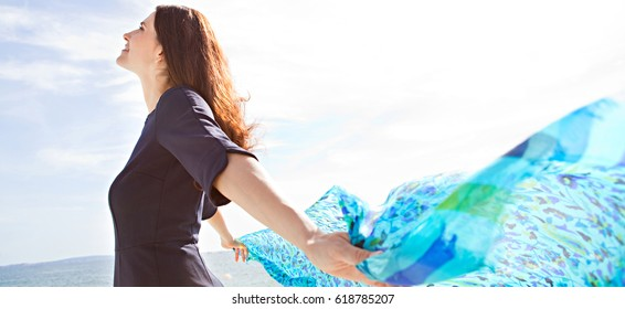 Panoramic portrait of beautiful mature woman breathing by the sea, rising a floating fabric scarf in the breeze on sunny day, outdoors. Well being and healthy lifestyle, dreamy positive exterior.