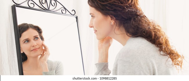 Panoramic portrait of beautiful middle age woman looking into mirror in bathroom applying cream on face, healthy grooming skin care cosmetics. Mature female reflection, stylish, wellness lifestyle.