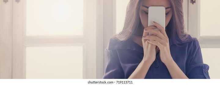 Panoramic portrait of Beautiful woman praying  and holding phone in the morning on windowsill .Religion, Spirituality and Prayer concept