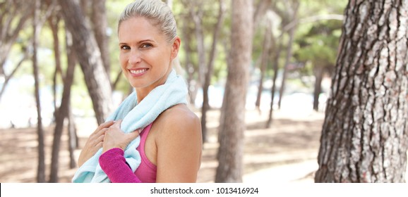 Panoramic portrait of beautiful woman recovering from exercising in park with towel around neck, looking and smiling in sunny outdoors. Healthy well being fitness, active sport leisure lifestyle.