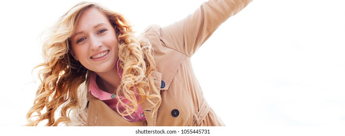 Panoramic portrait of a beautiful young woman smiling looking playful with arms outstretched against plain white sky background, outdoors. Healthy female, leisure recreation lifestyle, fresh beauty.