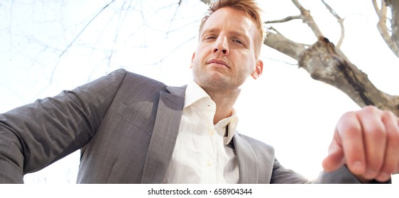 Panoramic portrait of powerful slick and attractive businessman sitting against a sunny sky in the city, looking at camera, confident and strong. Professional leader wearing smart suit, outdoors.