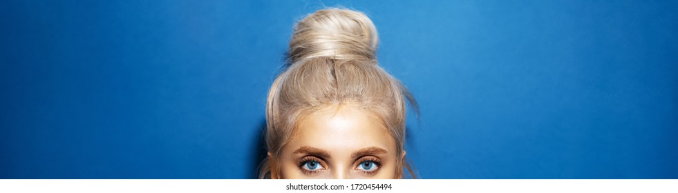 Panoramic portrait of woman head with blue eyes, blonde hair wrapped in a bun, on background of phantom blue color.