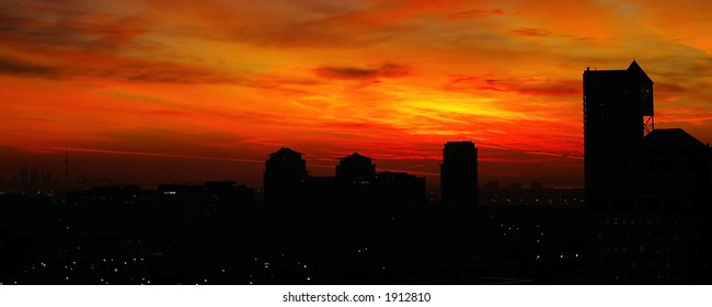 Panoramic Red, Orange, and Yellow cloudy sunrise over a city skyline (Mississauga & Toronto, Ontario).