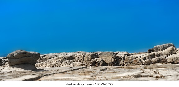 Panoramic rocky shoreline template with blue copy space