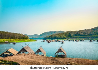 Panoramic scenery landscape view of bamboo raft hut floating restaurant on the beautiful tropical lake with mountains against colorful clear sky in background, tourist attraction in Loei, Thailand.
