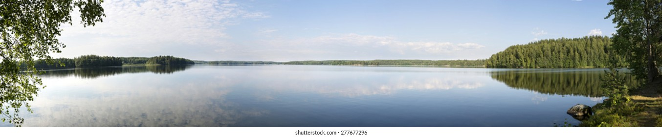 A panoramic scenery view of a shore of a Finnish lake in the summer in the day, with white clouds and the blue sky reflecting from the water.