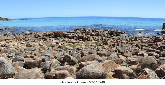 Panoramic scenic rocky landscape where the  Indian Ocean waves roll onto the rocky shore at isolated Bunker's Bay South Western Australia on a sunny afternoon  in early summer.