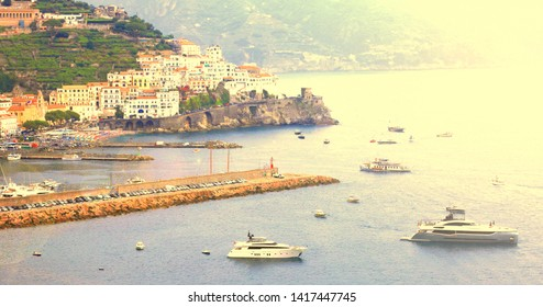 Panoramic scenic view of Amalfi Coast, Campania, Italy, in summer with traditional Italian architecture on mountains, beautiful blue sea and luxury yachts