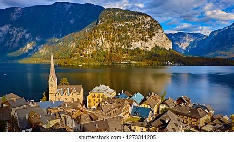 Panoramic scenic view in Austrian alps. Hallstatt mountain village at Hallstatt lake. Sunny day lake view from Hallstatt alps mountains. Location: resort village Hallstatt, Austria, Alps. Europe.