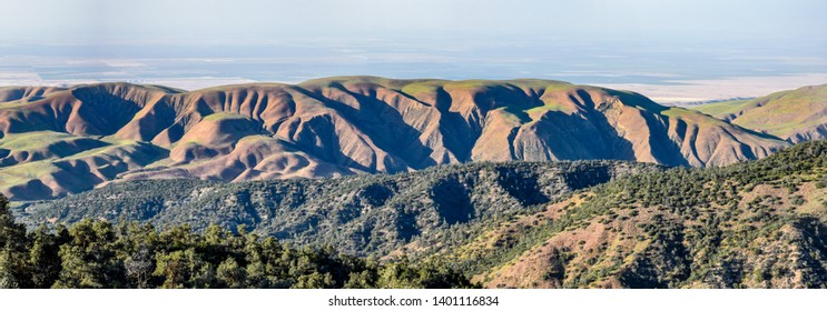 Panoramic scenic view of central California foothills overlooking San Joaquin Valley farmland. Warmer weather in spring causing grass to turn from green to brown