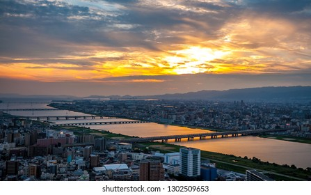 Panoramic, scenic view of Japan's Osaka city from the observatory deck of Umeda Sky Building during sunset with dramatic clouds in the blue and orange sky.