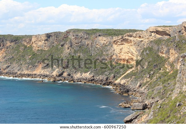Panoramic scenic view of the Southern Ocean looking down  from the  tall sparsely vegetated ancient limestone  cliffs at Windy Harbour Western Australia on a cloudy afternoon in mid summer.