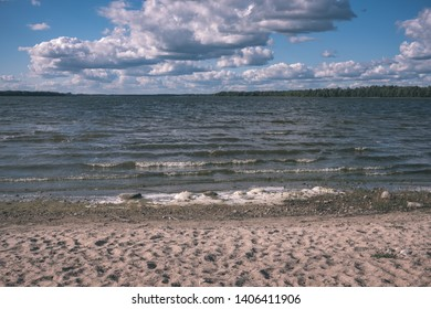 panoramic sea beach view in summer with rocks, plants and clean water in sunny day - vintage retro look