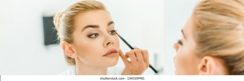 panoramic shot of blonde and beautiful woman applying eyeshadow with cosmetic brush