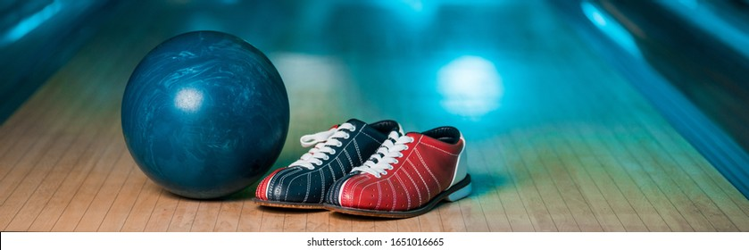 panoramic shot of bowling shoes and ball on skittle alley in bowling club