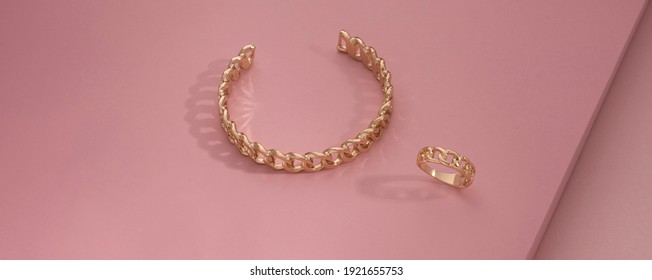 Panoramic shot of chain shape bracelet and ring on pink background