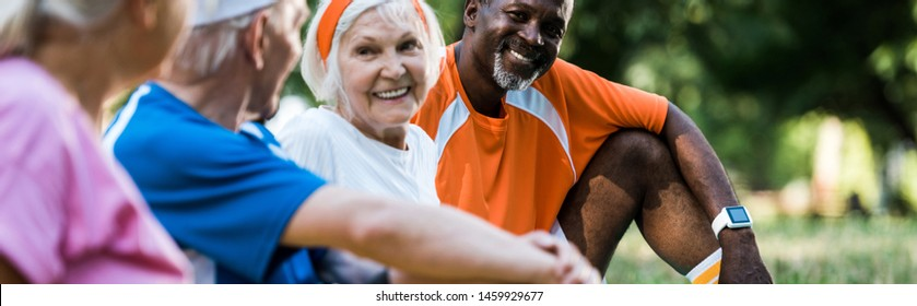 panoramic shot of cheerful multicultural men and women in sportswear