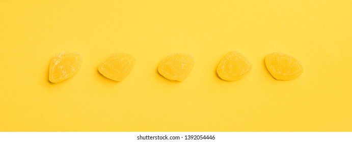 panoramic shot of delicious sugary jellies in row on yellow background