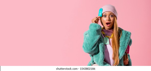 panoramic shot of excited, trendy african american woman touching label with sale inscription isolated on pink, fashion doll concept