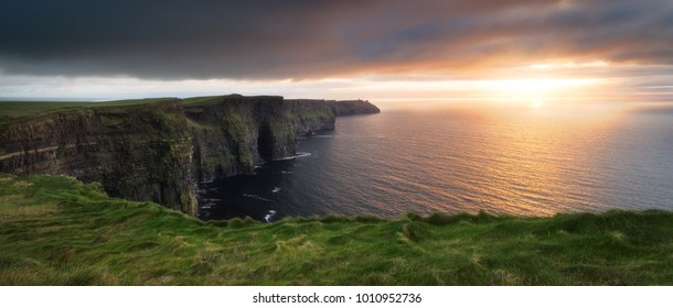 A panoramic shot of the famous Cliffs of Moher, in Ireland, photographed during the warm light of the sunset