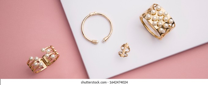 panoramic shot of flat lay of golden bracelets and ring on pink and white paper background
