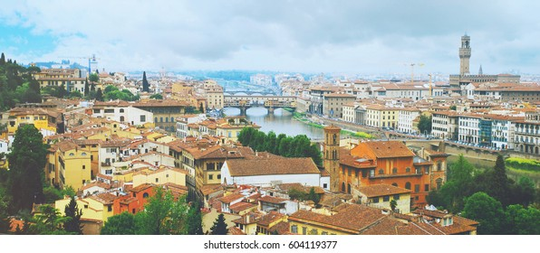 Panoramic shot of Florence seen from Michelangelo square: Arno River, Old Palace, Old Bridge and much roofs of cities buildings with cloudy blue sky