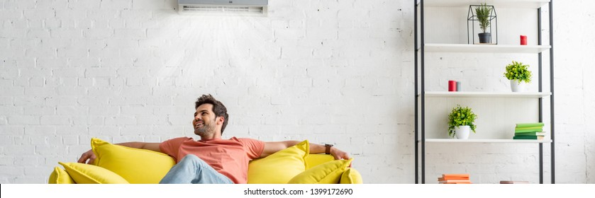 panoramic shot of handsome man sitting on yellow sofa under air conditioner at home