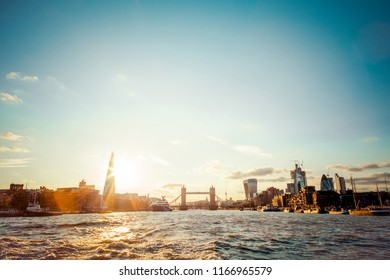 Panoramic shot of London skyline. Iconic Tower Bridge and skyscrapers from financial & business district on the background. View from the River Thames. Summer day. Orange sunset and blue sky.