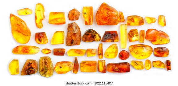 Panoramic shot of many pieces of amber with inclusions on a white background. Pieces of sunstone polished with different inclusions. Insects and larvae in frozen ancient resin. Color resin. Panorama