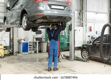 Panoramic shot of the mature car mechanic checking and repairing a lifted car in his garage. Checking and refilling the gearbox oil reservoir. Old car mechanics and repair concept.
