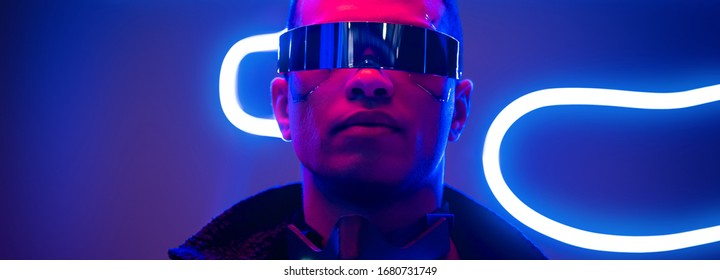 panoramic shot of mixed race cyberpunk player in futuristic glasses near blue neon lighting
