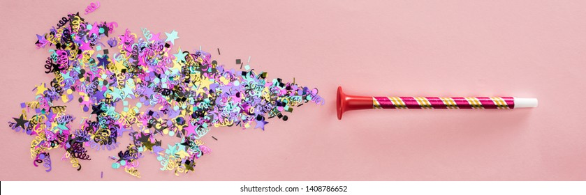 Panoramic shot of party horn with sparkling confetti on pink background