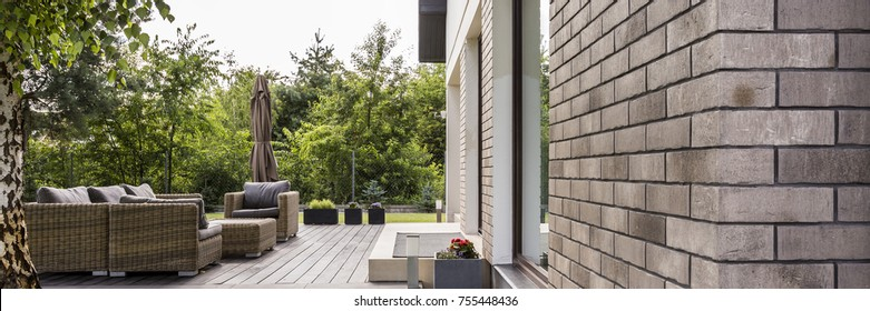 Panoramic shot of a patio with wooden floor and a rattan furniture set