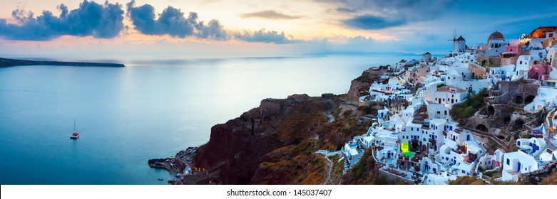 Panoramic shot at sunset over houses and villas at Oia Santorini Greece