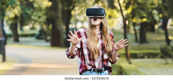 panoramic shot of surprised young girl in casual clothes using vr headset