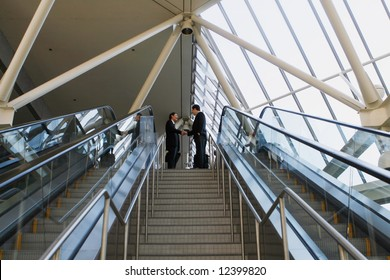 Panoramic shot of two businessmen shaking hands at the top of a stairway