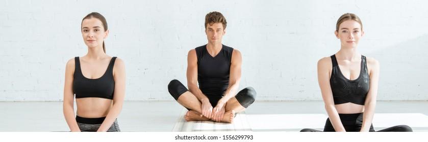 panoramic shot of young women and man practicing yoga in half lotus pose