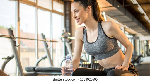 Panoramic side view of beautiful sporty girl in activewear holding bottle of water and taking a break after sports traning workout in gym