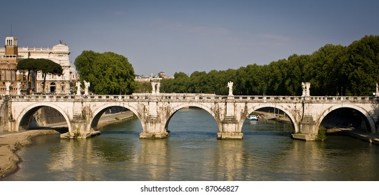 Panoramic side view of the Ponte Sant'Angelo bridge with the river Tiber flowing underneath it - Rome, Italy