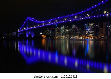 Panoramic side view of Story Bridge in Brisbane by night, with beautiful reflection in water