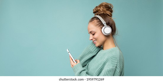Panoramic Side-ptofile closeup photo of beautiful young woman wearing stylish casual outfit isolated over colorful background wall wearing white wireless headphones and listening to music and using