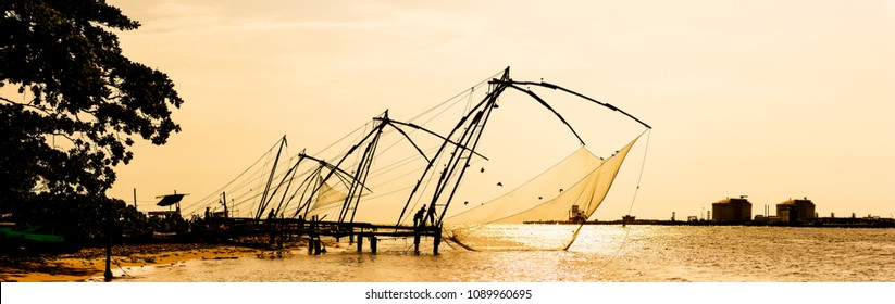 Panoramic silhouette of chinese fishnets on sunset at Fort Kochi, Kerala, India.