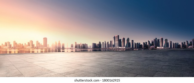 Panoramic skyline and buildings with empty space dark concrete square floor. Sunrise over the city view. City urban Landscape.