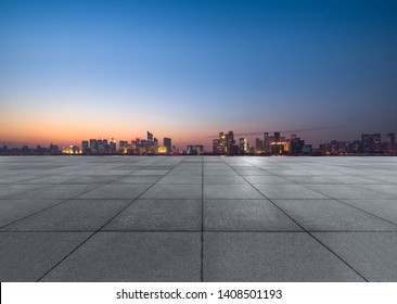 Panoramic skyline and buildings with empty square floor at dusk