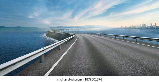 Panoramic Skyline Landscape over the sea and city with empty space asphalt road. Highway overpass motion blur effect with with cityscape in background. Empty highway through modern city seascapes.